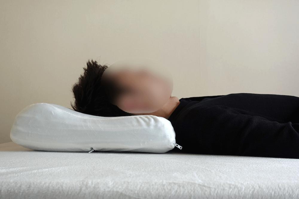 モットンの枕に男性が仰向けで寝た様子